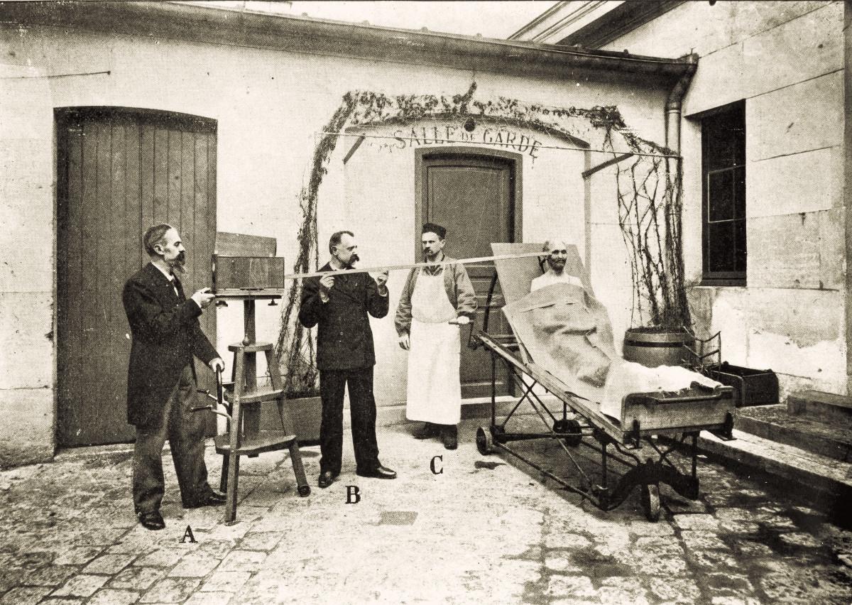 Essa cena mostra a metodologia usada para fotografar um cadáver antes de uma autópsia.
