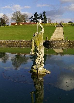 A estátua de netuno sobre a cúpula de vidro no meio do lago