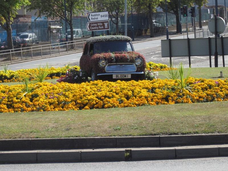 Uma mini rotatória na ilha de Longbridge, Birmingham, tem um velho carro Mini florido no centro. | Crédito da foto